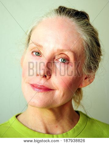 Mature female blond beauty expressions alone indoors.