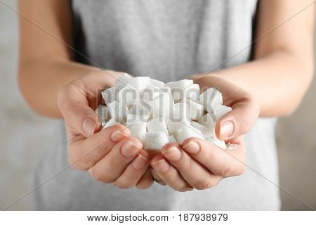 Female hands holding sugar cubes, closeup