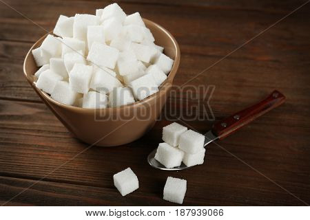 Bowl with sugar cubes and spoon on wooden table