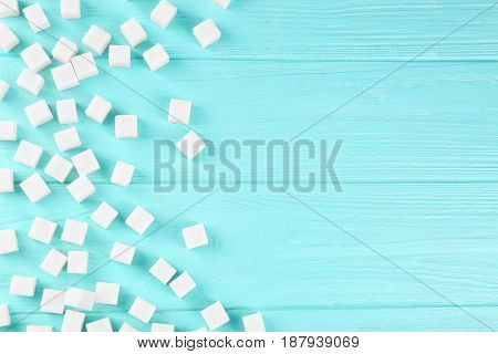 Scattered sugar cubes on wooden table