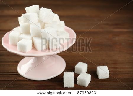 Stand with sugar cubes on wooden table