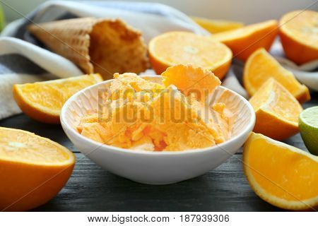 Bowl with delicious ice-cream and oranges on wooden table