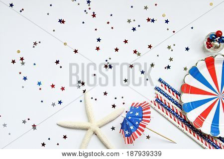 Festive red, white and blue picnic supplies and decorations frame open copy space with star confetti