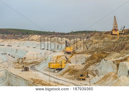 Work of heavy grab and bucket excavators in the chalk quarry. Heavy mining industry.