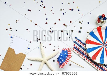 Festive red, white and blue picnic supplies and decorations frame confetti space for copy