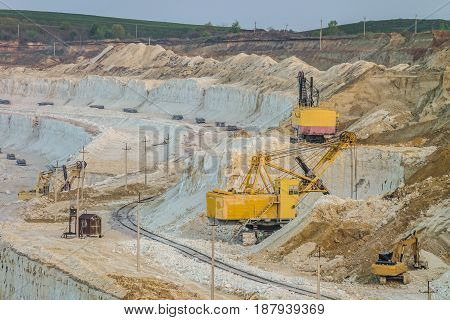 Heavy mining excavators in the chalky quarry. Heavy chalk mining industry.