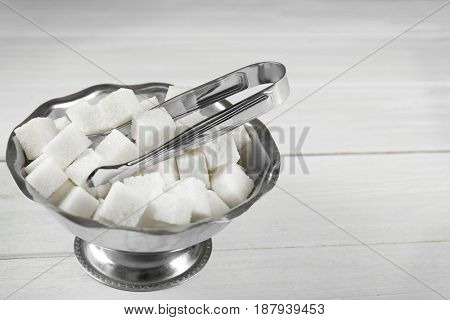 Bowl with sugar cubes and forceps on wooden table