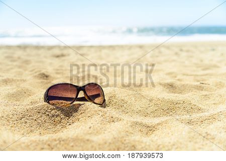 Close up sunglasses on the beach on warm yellow sand, with luring water sparkling on background