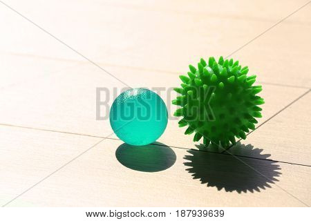 Two rubber balls on light wooden background