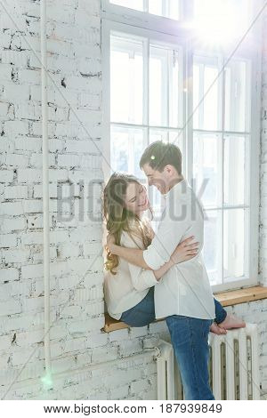 Young couple in love. Couple supporting each other and relying on each other having nice time together. Young happy woman hugging her handsome boyfriend. Portrait of cheerful casual people in love, students having hopes, dreams, goals, bride and groom
