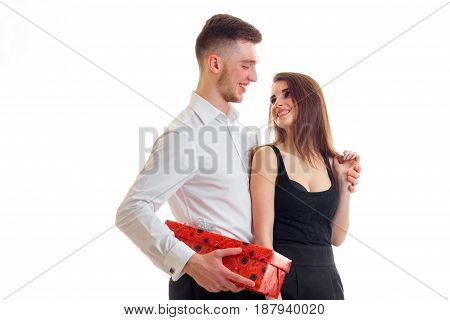 a charming young girl in a dress and looking at the beautiful guy in the shirt and with a gift in hand isolated on white background.
