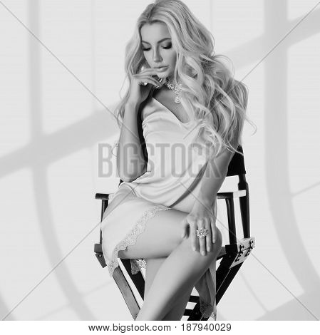 Young stunning and sexy tanned blonde woman with long curly hair wearing bright micro tunic dress and sitting in high directors chair. Sun light with beautiful shadows. Fashion portrait.