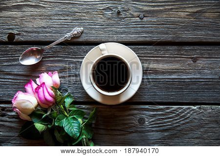 cup of coffee with red rose and and copy space on wood background. breakfast on Mothers day, Women's day, valentine's day or birth day. hot drink, flowers
