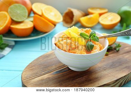 Delicious citrus ice cream with slices of orange and mint in bowl on cutting board