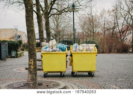 Two yellow garbage containers on a street in Germany. Collection and disposal of domestic waste. Ecology.