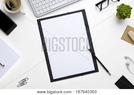 Overhead view of folder surrounded with office supplies on white desk