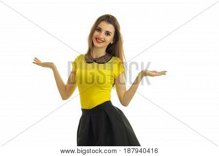 cute pin-up girl in bright clothes stands straight smiles and holds the Palm of your hand on the sides of the isolated on white background.