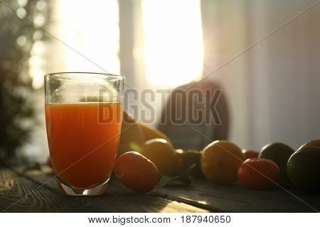 Glass of juice and fresh citrus fruits on wooden table near window