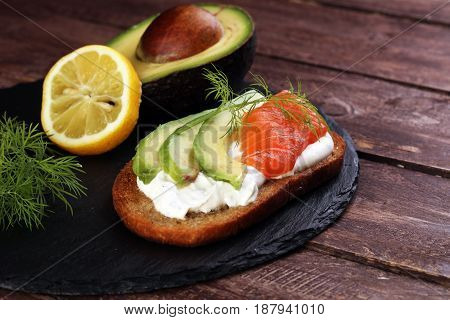 Bread With Avocado And Smoked Salmon For Lunch Table. Sharing Antipasti On Party Or Summer Picnic Ti