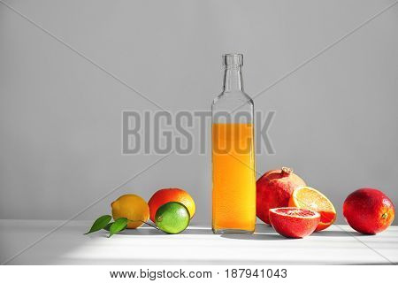 Beautiful composition with citrus fruits and juice on light background