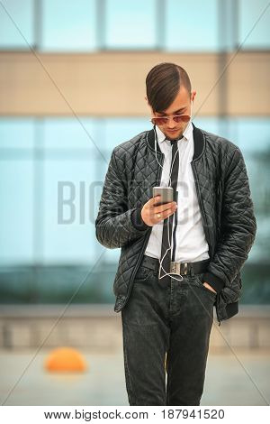 Portret Of A Handsome Young White Guy With Modern Haircut In Aviator Sunglasses And Headphones With