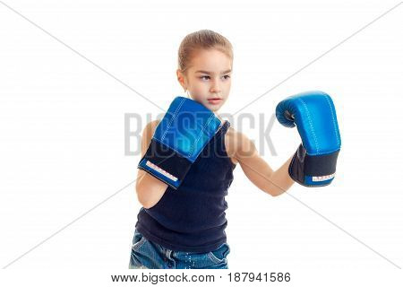 little girl standing in front of the camera in large boxing gloves is isolated on a white background close-up
