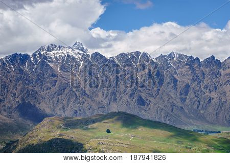 Winding path leading over a grassy hill. Jagged mountain range and moody clouds in background. Queenstown New Zealand