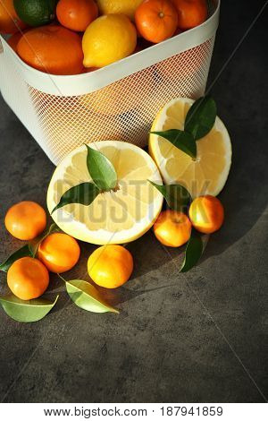 Plastic basket with fresh citrus fruits and halves of pomelo on table
