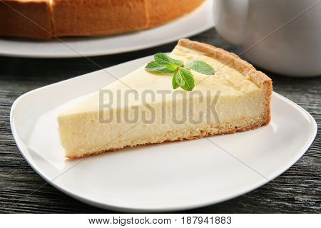 Plate with piece of tasty cheesecake on wooden table, closeup