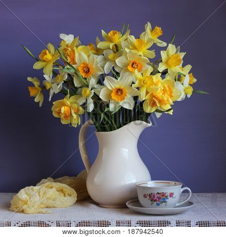 Fresh bouquet of yellow daffodils in a white jug and a retro Cup on the table in front of purple background.