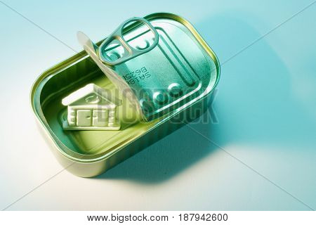 Tin Can with Miniature House on  Blue Background
