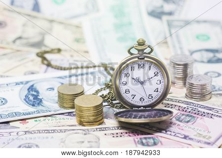 Classic pocket watch coins with banknotes 10 dollar 50 dollar for realestate business and financial concept.