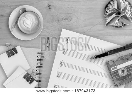 music sheet cactus fountain pen tape cassette and coffee latte on wooden table top view picture