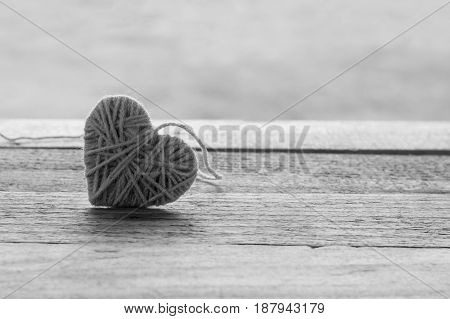 pink knitting wool in shape of heart on vintage wooden with bokeh soft light background