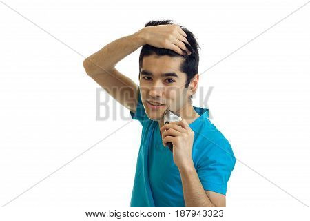 Portrait of smiling charming guy who keeps hand hair and shaves isolated on a white background close-up