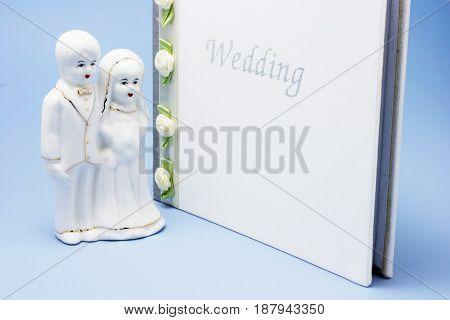Wedding Couple Figurine and Photo Album on Blue Background