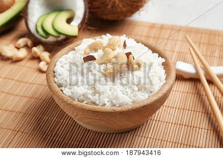 Tasty coconut rice with cashew nuts on bamboo mat