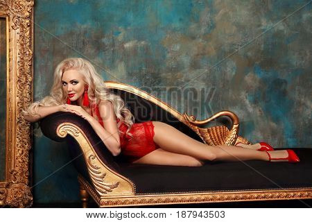 Beautiful Alluring Young Blonde Woman In Sexy Red Lingerie Lying On Royal Sofa In Luxury Modern Inte
