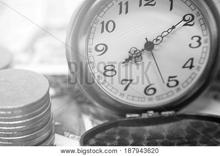 classic pocket watch and coins on dollar banknote concept and idea of time value and money business and finance concepts.