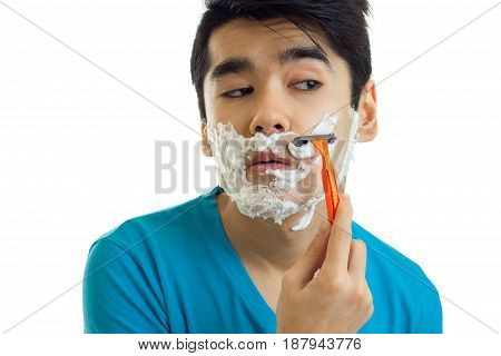 Portrait of a ridiculously young man in a t-shirt who looks away with foam on your face and shaves his beard machine is isolated on white background.