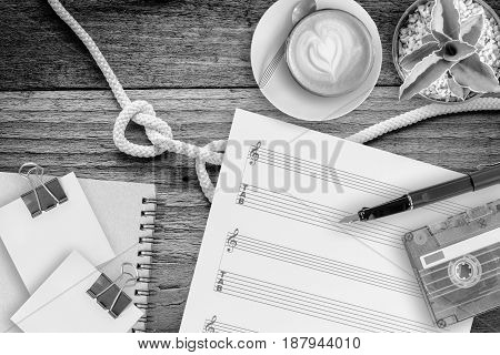 music sheet cactus fountain pen tape cassette and coffee latte on vintage wooden table