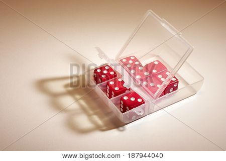 Red Dice in Plastic Container on Warm Background