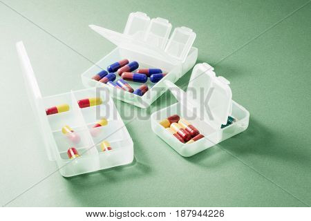 Pills in Pill Boxes on Green Background