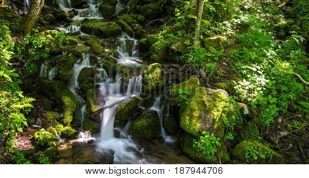 Smoky Mountain Waterfall. Mountain stream tumbles down the mountain side surrounded by lush green foliage. The Smoky Mountains are considered a rain forest and are America's most visited national park