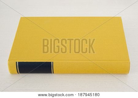 Yellow book with black frame on spine on the bright wooden table