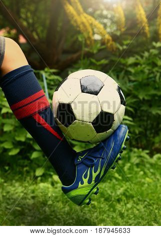kid boy foot in soccer boot and ball on green grass background