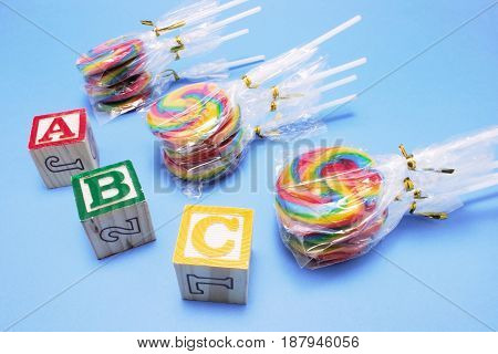 Lollipops with Alphabet Blocks on Blue Background