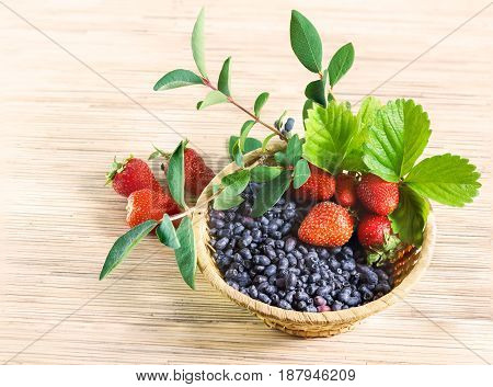 Berries red ripe strawberry and blue honeysuckle far East in a wicker basket with leaves on the table