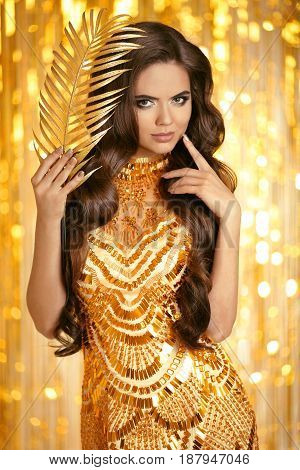 Elegant Brunette In Golden Dress. Fashion Style. Beauty Makeup And Wavy Hairstyle. Beautiful Smiling