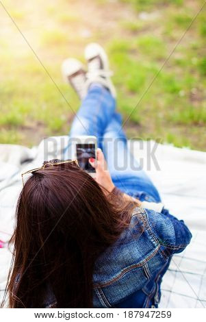 A young girl with a smartphone from the back with long hair in jeans clothes and sneakers on a plaid in a sunset light blurred image.